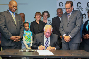 Jennifer Cushman (back, second from left) watches as Gov. Pat Quinn signs the Illinois Homeless Bill of Rights at the CCH office, on August 22, 2013. (Photo by Judy Fidkowski)