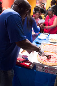 Organizer Keith Freeman serves pizza to the poets and guests.