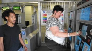 Unity Parenting and Counseling supervisor Anne Holcomb buys single-ride Ventra tickets from a vending machine at a CTA Green Line station Aug. 22, 2016, as James Ivory, left, a client with the social service agency, looks on. (Antonio Perez / Chicago Tribune)