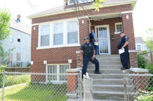 Cook County Sheriff's Police Officer James Clemmons and Officer Kevin Johnson stand outside of a home where they had to serve people with eviction papers. (Photo by Brian Jackson/Sun-Times)