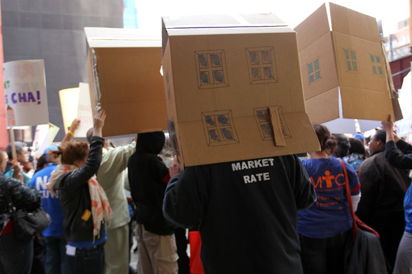 Protesters hold cardboard houses over their heads while supporting families on the waiting lists for Chicago Housing Authority apartments during a rally in front of CHA headquarters on Van Buren Street in Chicago on April 24, 2012. (Scott Strazzante / Chicago Tribune / April 24, 2012)