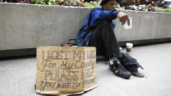 Mike Droney, a homeless veteran, displays a redesigned cardboard sign in downtown Chicago on July 2, 2015. (Michael Noble Jr., Chicago Tribune)